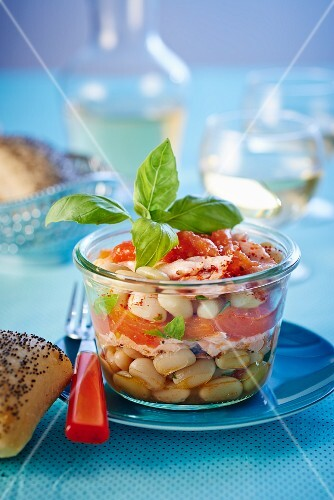 White beans with salmon and basil in a jar