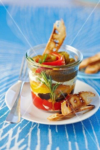 Peppers with olives and cheese cream in a glass served with bread crisps