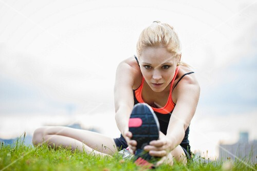 A sporty young woman stretching in a field