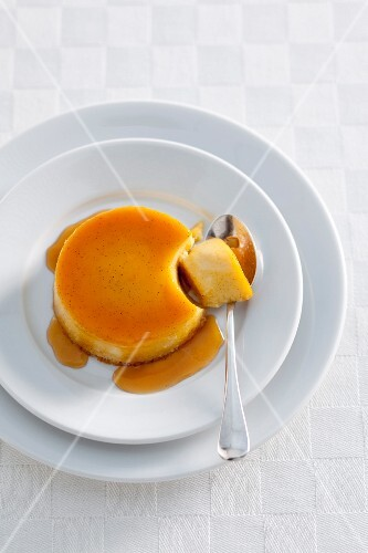 Caramel pudding with a piece on a spoon