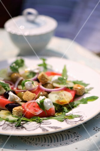 Melon and goat's cheese salad with olives, croutons, cucumber and rocket