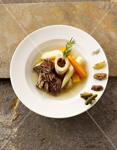 Beef stock with bone marrow dumplings and super vegetables with cornichons and mustard on the edge of the plate