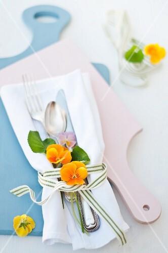 Gelbe und violette Hornveilchenblüten als Tischdeko mit Besteck auf weisser Stoffserviette