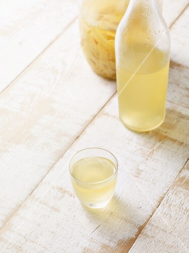Homemade lemoncillo (Italian liqueur) in a glass and in a jug