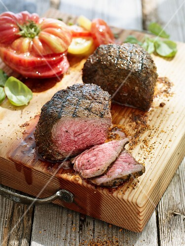 Beef fillet with tomatoes and basil on a chopping board