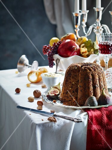 Figgy pudding, a bowl of fruit and wine on a table laid for Christmas