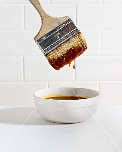 A brush being dipped in a bowl of barbecue sauce