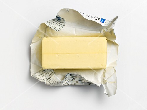 An unwrapped pat of butter on its wrapper