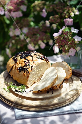 Sliced onion bread on a wooden plate for a picnic