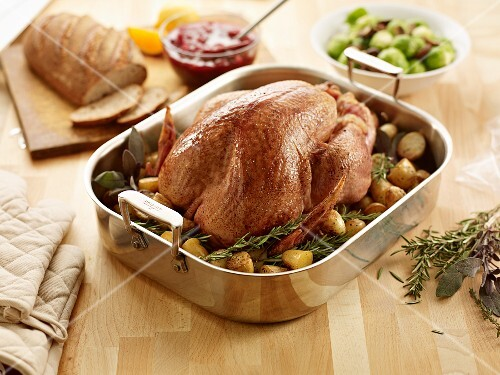 Roast turkey with potatoes and rosemary in a roasting tin