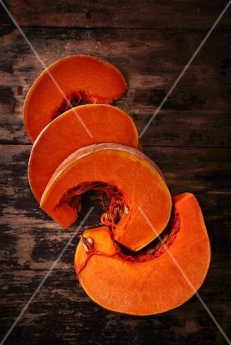 Pumpkin wedges on a wooden surface
