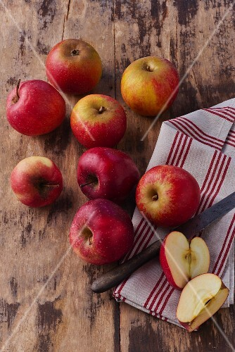 Fresh red apples with a tea towel and knife