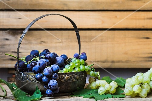 Red and green grapes in a metal basket