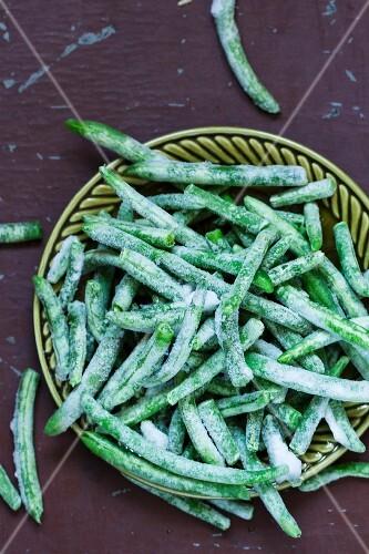 Frozen green beans on a green plate