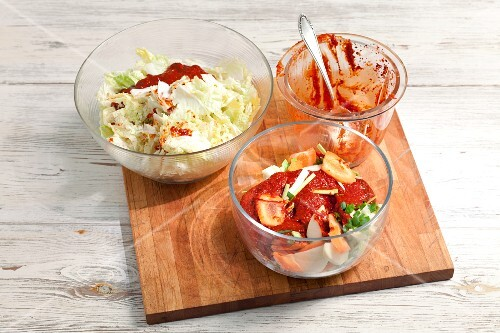 Sliced vegetables with chilli paste and salted Chinese cabbage on a chopping board (ingredients for kimchi)