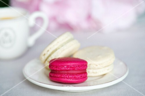 Three macaroons, pink and white, on a saucer