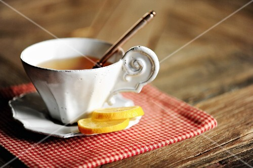 A cup of hot tea with two slices of lemon