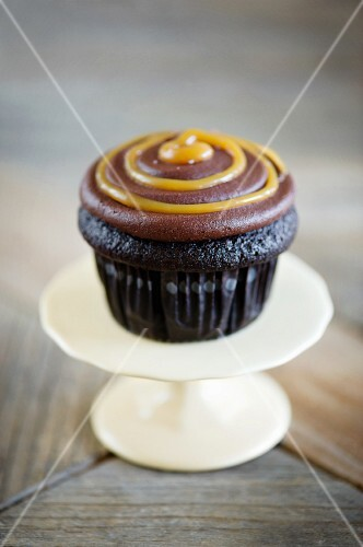 A chocolate cup cake with a chocolate and caramel topping on a mini cake stand