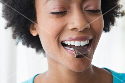 A smiling woman holding a piece of chocolate between her teeth