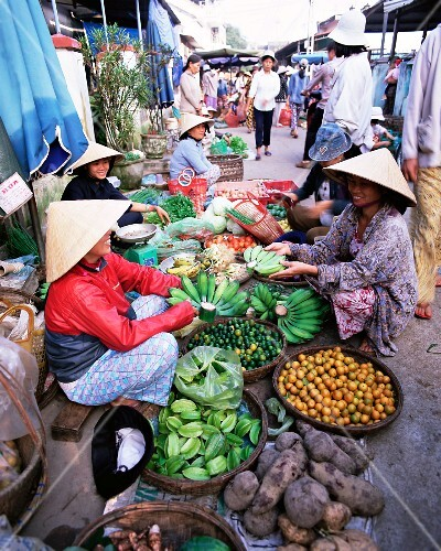 Women wearing conical hats selling fruit and vegetables in the busy central market, Hoi An, Central Vietnam, Vietnam, Indochina, South-East Asia