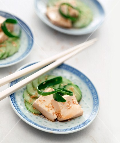 Tofu with sesame seeds and ginger on a bed of cucumber slices