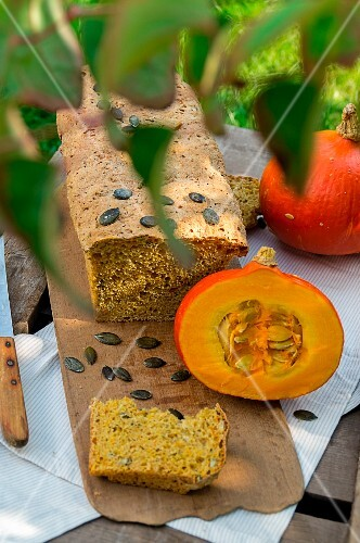 Pumpkin bread with pumpkin seeds and a Hokkaido pumpkin on a chopping board
