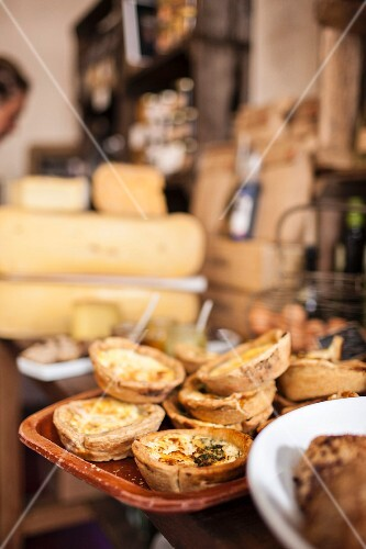 Mini cheese quiches, a selection of cheese and wine in a delicatessen