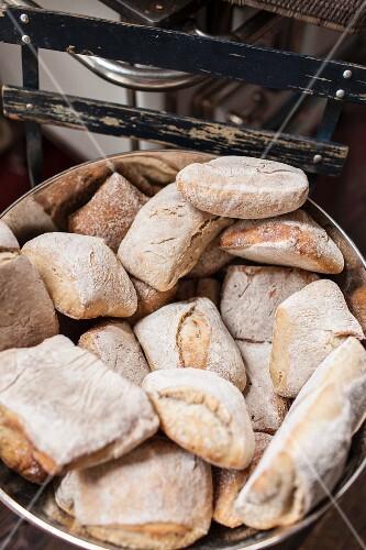 Bread rolls in a metal bowl in a baker's