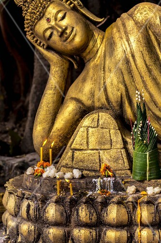 Sticky rice, candles and flowers in front of a Buddha statue (Vientiane, Laos)