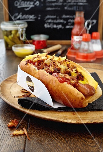 A hotdog with cheese and ketchup at a fast food cafe