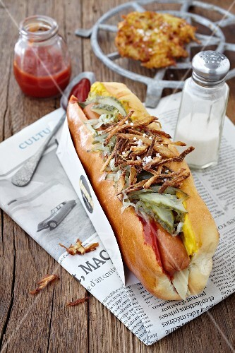 A hot dog with gherkins, onions, ketchup and honey mustard