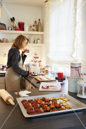 A woman baking Christmas biscuits in a kitchen