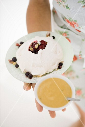 A woman holding a meringue with berries and cardamom cream