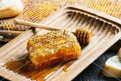 Honeycomb with a honey spoon in an old wooden bowl