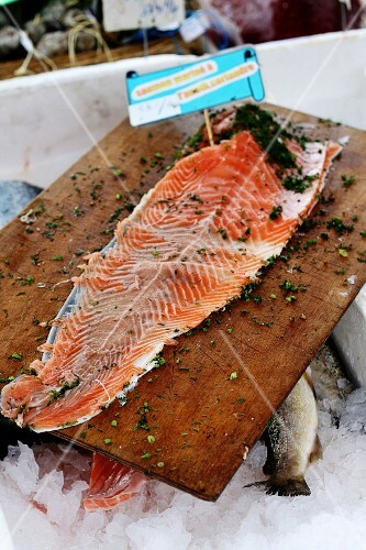 Salmon fillet with herbs on a wooden chopping board