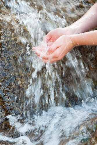 Person holding their hands under the flowing water of a mountain stream