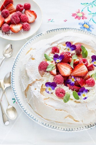 Pavlova with berries and violets