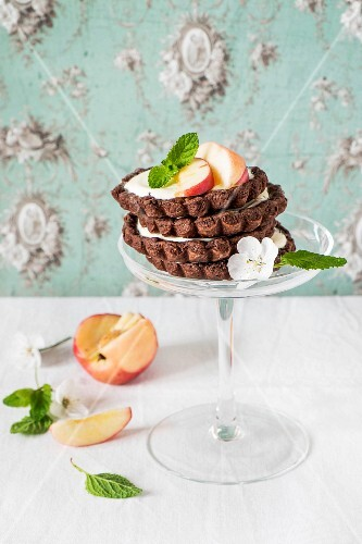 A stack of chocolate tartlets with peaches and cream cheese
