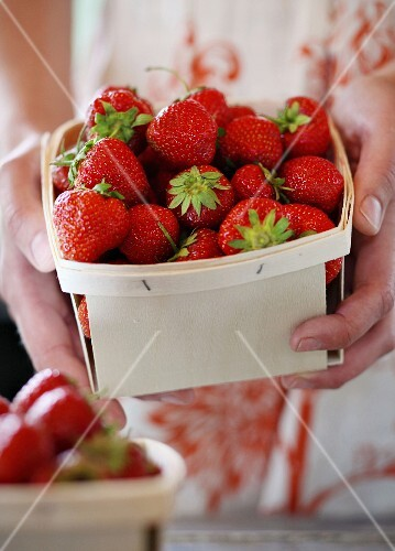 Hands holding a wooden punnet of strawberries