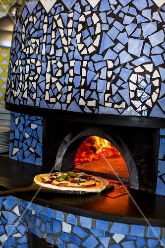A pizza margherita being push into an oven (Pizzeria Sorbillo, Naples, Italy)
