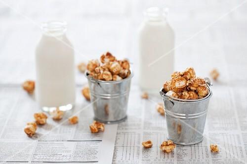 Small buckets of caramel popcorn and bottles of milk