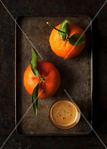 Two clementines and a glass of coffee on a tray