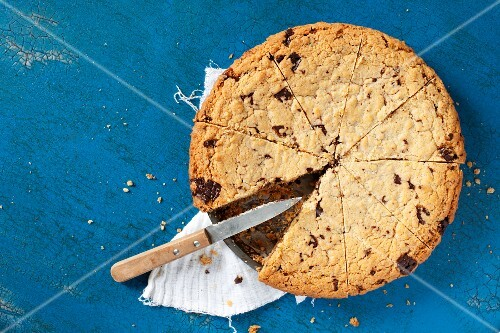 A chocolate chip cookie cake in the tin with a piece missing