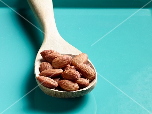 Unshelled almonds on a wooden spoon