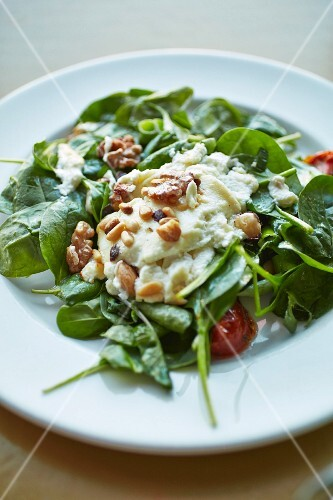 Spinach salad with hummus dressing, tomatoes and nuts