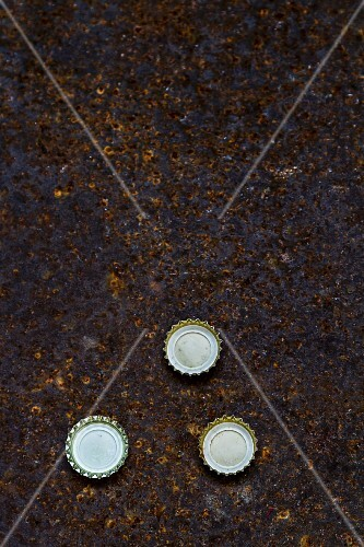Three beer bottle caps on a piece of rusty metal