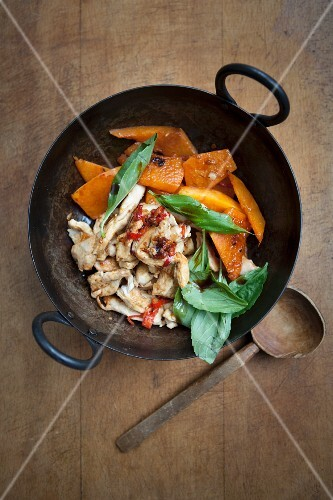 Chicken with pumpkin and basil in a wok