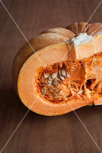 A halved giant pumpkin on a wooden surface