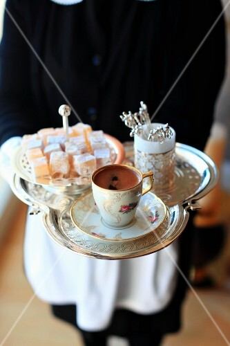 A waitress serving coffee with Turkish delight