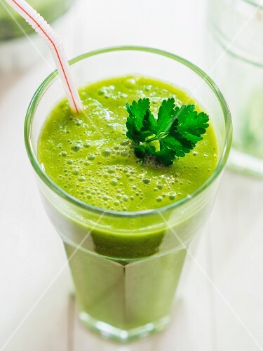 A gGreen smoothie garnished with parsley